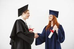 Two graduates classmates shake hands smiling holding diplomas over white background. Royalty Free Stock Image