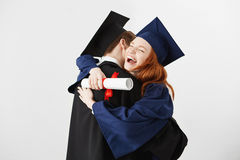 Two graduates embracing over white background. Ginger girl laughing looking at camera. Stock Photos