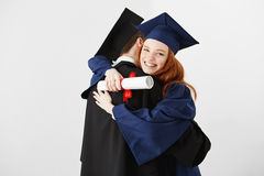 Two graduates embracing over white background. Ginger girl smiling looking at camera. Royalty Free Stock Images