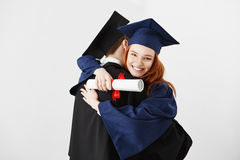 Two graduates embracing over white background. Ginger girl smiling looking at camera. Stock Photography