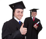 Two graduates with the first showing a thumbs up sign and the se. Two graduates with a selective focus used on the first one which is showing a thumbs up sign Stock Image