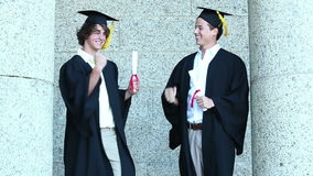Two graduates giving highfive. And embracing each other stock video