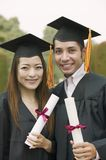 Two graduates holding diplomas outside portrait Stock Image