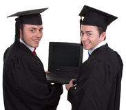 Two graduates holding a laptop looking around, isolated on white Stock Images