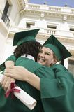 Two graduates hugging outside university Royalty Free Stock Photography
