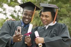 Two graduates looking at cell phone outside stock photos