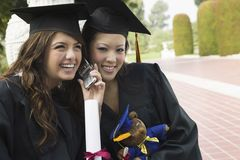 Two Graduates Using Cell Phone Outside Royalty Free Stock Photography