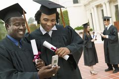 Two Graduates Using Cell Phone Outside Royalty Free Stock Images
