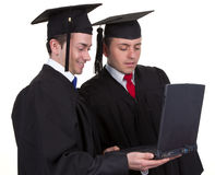 Two graduates working together on a laptop, isolated on white Royalty Free Stock Images