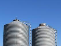Two Grey Metal Grain Bins Against a Blue Sky Stock Photo