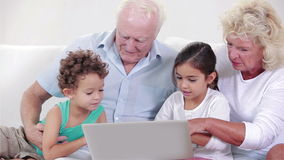 Two grandparents and two children using a laptop. On the couch stock video footage