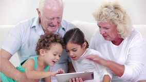 Two grandparents and two children using a tablet. Witht their grandchildren stock video