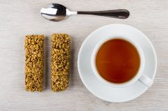 Two granola bar, tea in cup on saucer, teaspoon. On wooden table. Top view Royalty Free Stock Photography
