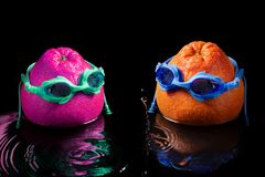 Two grapefruit in swimming goggles, like a man and a woman, stand in water, splash and drops, the concept of family recreation and stock photo