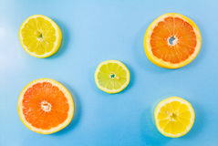 Two grapefruit and three lemon slices on blue background. Minimalist picture style with some copyspace for text Royalty Free Stock Photography