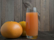 Two grapefruits with glass of juice. With wooden background Royalty Free Stock Images