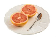 Grapefruits on plate with spoon. Two grapefruits on old white plate with spoon on white background Royalty Free Stock Photography
