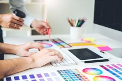 Two Graphic designer drawing on graphics tablet and color palett stock images