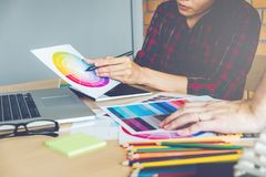 Two Graphic designer drawing on graphics tablet and color palette guide at workplace.  royalty free stock photography