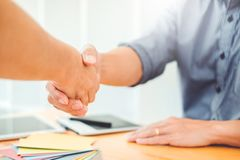 Two Graphic designer handshake Meeting and drawing on graphics t. Ablet at workplace royalty free stock photos