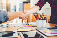 Two Graphic designer handshake Meeting and drawing on graphics t. Ablet at workplace stock photo