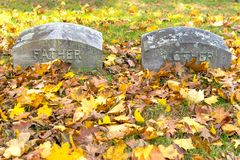 Two gravestones, inscribed with the words Father & Mother, amid green grass and fallen foliage on a sunny fall day in stock images