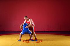 Two young man  wrestlers. Two greco-roman  wrestlers in red and blue uniform making a   hip throw  on a yellow wrestling carpet in the gym Stock Photos