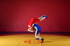 Two greco-roman wrestlers. In red and blue uniform wrestling on a yellow wrestling carpet in the gym Stock Photography
