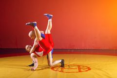 Two greco-roman wrestlers. Two greco-roman  wrestlers in red and blue uniform wrestling   on a yellow wrestling carpet in the gym Stock Image