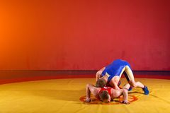 Two young men  wrestlers. Two greco-roman  wrestlers in red and blue uniform wrestling   on a yellow wrestling carpet in the gym Stock Photo