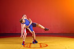 Two young men wrestlers. Two greco-roman wrestlers in red and blue uniform wrestling on a yellow wrestling carpet in the gym royalty free stock photography