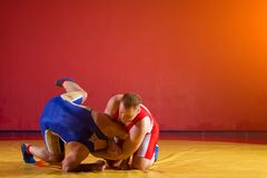 Two young men  wrestlers. Two greco-roman  wrestlers in red and blue uniform wrestling   on a yellow wrestling carpet in the gym Stock Photos