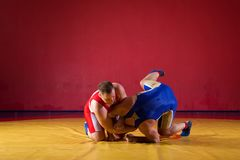 Two young men wrestlers. Two greco-roman wrestlers in red and blue uniform wrestling on a yellow wrestling carpet in the gym royalty free stock image