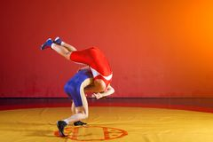 Two greco-roman wrestlers. Two greco-roman  wrestlers in red and blue uniform wrestling   on a yellow wrestling carpet in the gym Royalty Free Stock Images