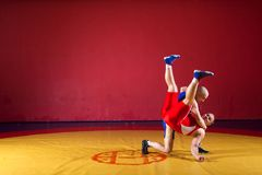 Two greco-roman wrestlers. Two greco-roman  wrestlers in red and blue uniform wrestling   on a yellow wrestling carpet in the gym Royalty Free Stock Image