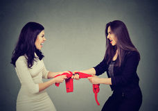 Two greedy women fighting for red tank-top on gray wall background. Two greedy women fighting for red tank-top Stock Images
