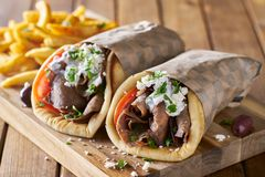 Two greek gyros with shaved lamb and french fries royalty free stock images