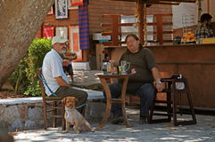 Two Greek men sit at a rustic outdoor cafe(Crete,Greece) Royalty Free Stock Photography