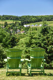 Two green adirondack chairs face the hills Royalty Free Stock Image