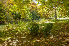 Two Green Adirondack Chairs Beside a Pond Stock Photo