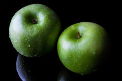 Two green apples on black from high angle Stock Image