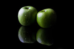 Two green apples on black from side with reflection Stock Image