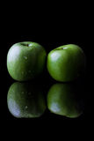 Two green apples on black from side with reflection vertical Royalty Free Stock Image