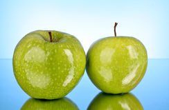 Two green apples on blue Stock Photo