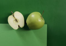 Two green apples on geometric green background. Still life Royalty Free Stock Photography