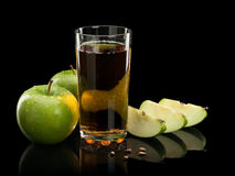 Two green apples, juice and three parts of an apple Stock Images