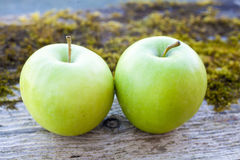 Two green apples on the old Board Stock Images