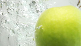 Two Green Apples Plunging Into Water. Two whole fresh tasty green apples plung in water on white background breaking liquid surface with explosive stunning stock video footage
