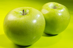 Two green apples. On a green table stock image