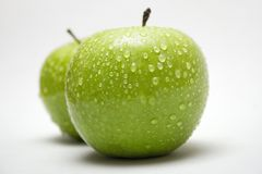 Two Green Apples w/ Raindrops (Side View). Raindrops on two delicious green apples Royalty Free Stock Photos